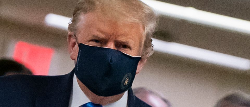 US President Donald Trump wears a mask as he visits Walter Reed National Military Medical Center in Bethesda, Maryland. ALEX EDELMAN/AFP via Getty Images