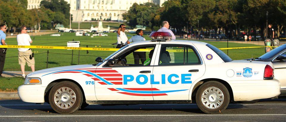 A Washington police car arrives at the scene where a man set himself on fire near the U.S. Capitol on the U.S. National Mall in Washington