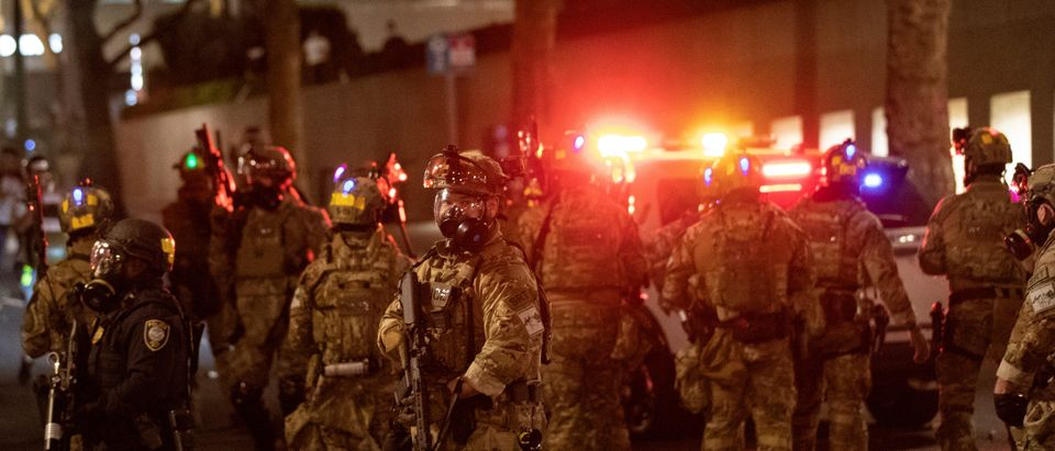 Federal law enforcement officers deployed under the Trump administration's executive order face off with protesters