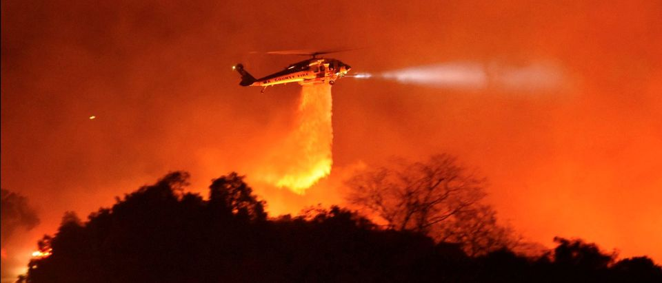 A Los Angeles County Firehawk helicopter makes a water drop on flames during the Cave fire in Los Padres National Forest near East Camino Cielo