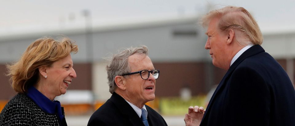 U.S. President Donald Trump shakes hands with Governor of Ohio Mike DeWine as he arrives at Akron-Canton airport in Canton, Ohio, U.S.