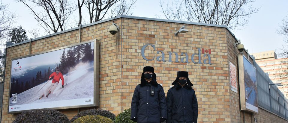 """Chinese police officers stand guard outside the Canadian embassy in Beijing on December 10, 2018. - China on December 10 protested Canada's """"inhumane"""" treatment of an executive of telecom giant Huawei who is being held on a US extradition bid, following reports she was not getting sufficient medical care. (Photo by Greg Baker/AFP via Getty Images)"""