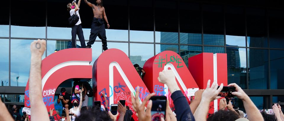 ATLANTA, GA - MAY 29: A man waves a Black Lives Matter flag atop the CNN logo during a protest in response to the police killing of George Floyd outside the CNN Center on May 29, 2020 in Atlanta, Georgia. Demonstrations are being held across the U.S. after George Floyd died in police custody on May 25th in Minneapolis, Minnesota. (Elijah Nouvelage/Getty Images)