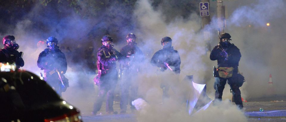 "Security personnel stand in a cloud of tear gas in Portland, Oregon early July 26, 2020, as protests continue across the United States following the death in Minneapolis of unarmed African-American George Floyd. - Police and federal agents fired tear gas and forcefully dispersed protesters in the US city of Portland, amid President Donald Trump's heavily-criticized ""surge"" of security forces to major cities. The city, the biggest in the state of Oregon, has seen nightly protests against racism and police brutality for nearly two months, initially sparked by the death of unarmed African American George Floyd at the hands of police in Minnesota (Photo by Ankur Dholakia/AFP via Getty Images)"