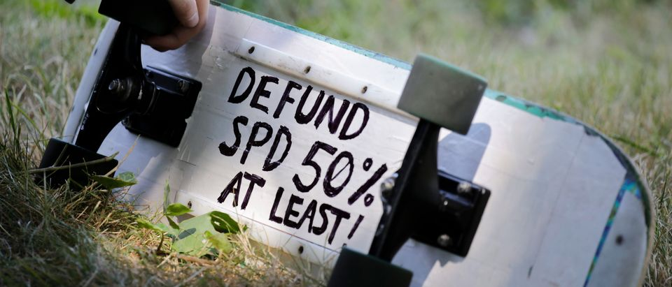 "A defund Seattle Police Department (SPD) sign is pictured on a protester's skateboard during a ""Defund the Police"" march from King County Youth Jail to City Hall in Seattle, Washington on August 5, 2020. (Photo by Jason Redmond/AFP via Getty Images)"