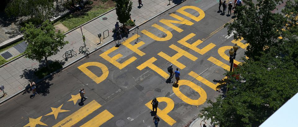 """People walk down 16th street after """"Defund The Police"""" was painted on the street near the White House on June 08, 2020 in Washington, DC. (Tasos Katopodis/Getty Images)"""