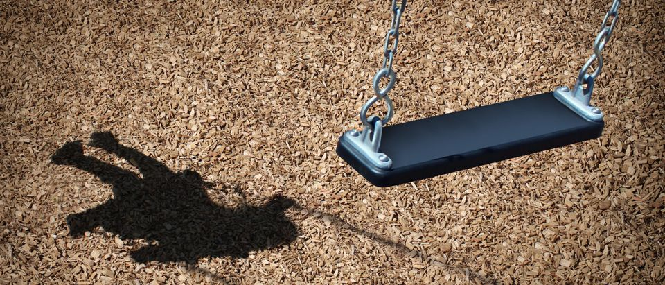Missing child concept with an empty playground swing and the shadow of a little girl on the park floor as a symbol of children losing their childhood as being lost in a failed adoption or despair (Shutterstock/Lightspring)