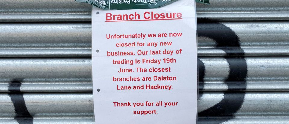 A sign announcing the closure of a branch of Travis Perkins is seen attached to shutters at the business premises in London