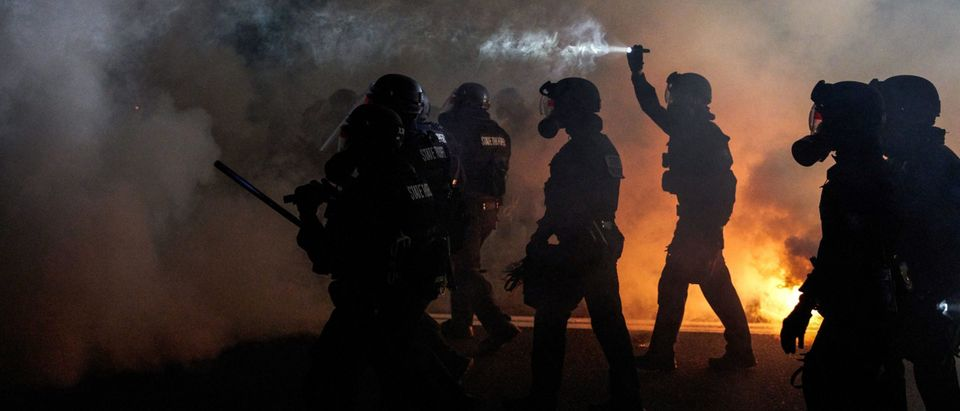 Oregon Police wearing anti-riot gear march towards protesters through tear gas smoke during the 100th day and night of protests against racism and police brutality in Portland, Oregon, on September 5, 2020. - Police arrested dozens of people and used tear gas against hundreds of demonstrators in Portland late on September 5 as the western US city marked 100 days since Black Lives Matter protests erupted against racism and police brutality. Protests in major US cities erupted after the death of African American George Floyd in May 2020 at the hands of a white police officer in Minneapolis. (Photo by Allison Dinner/AFP via Getty Images)