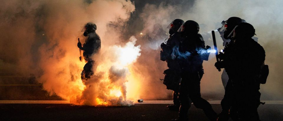 TOPSHOT - Oregon Police wearing anti-riot gear march towards protesters through tear gas smoke during the 100th day and night of protests against racism and police brutality in Portland, Oregon, on September 5, 2020. - Police arrested dozens of people and used tear gas against hundreds of demonstrators in Portland late on September 5 as the western US city marked 100 days since Black Lives Matter protests erupted against racism and police brutality. Protests in major US cities erupted after the death of African American George Floyd in May 2020 at the hands of a white police officer in Minneapolis. (ALLISON DINNER/AFP via Getty Images)