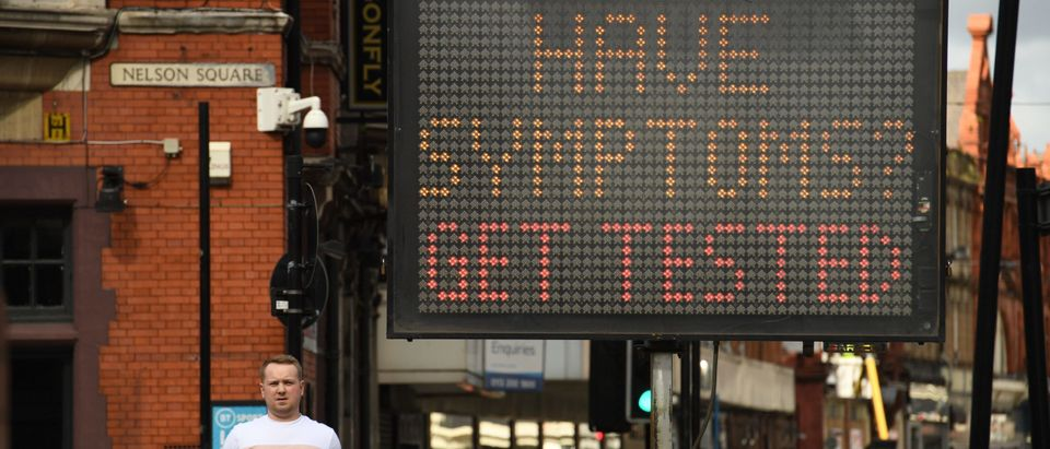 Pedestrians pass an electronic board urging people to seek a test if they have Covid-19 symptoms in Bolton, northwest England on September 9, 2020. (Photo by OLI SCARFF/AFP/Getty Images)