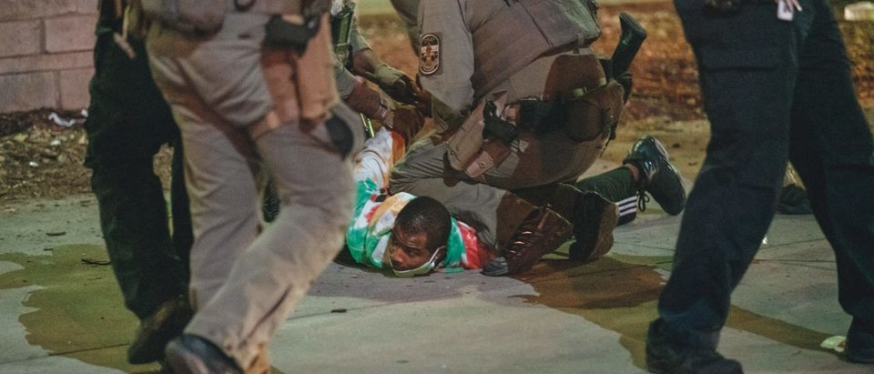 LOUISVILLE, KY - SEPTEMBER 23: A protester is detained shortly after shots are fired at police, resulting in two injured officers, on September 23, 2020 in Louisville, Kentucky. Protesters took to streets after Kentucky Attorney General Daniel Cameron's announcement to indict only one of the three LMPD officers involved in the death of Breonna Taylor during a no-knock raid executed on her apartment on March 13, 2020. (Jon Cherry/Getty Images)
