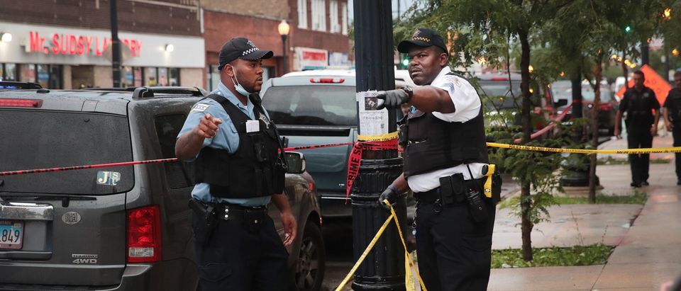 CHICAGO, ILLINOIS - JULY 21: Police secure the scene of a shooting in the Auburn Gresham neighborhood on July 21, 2020 in Chicago, Illinois. At least 14 people were transported to area hospitals after several gunmen opened fire on mourners standing outside of a funeral home. More than 2000 people have been shot and more than 400 have been murdered in Chicago so far this year. (Scott Olson/Getty Images)