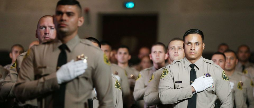 MONTEREY PARK, CALIFORNIA - AUGUST 21: Graduates of Los Angeles County Sheriff's Department Academy Class 451 stand for the pledge of allegiance at their graduation ceremony at East Los Angeles College amid the COVID-19 pandemic on August 21, 2020 in Monterey Park, California. Graduates were seated with social distancing and family members were not allowed inside the ceremony due to restrictions in place to prevent the spread of the coronavirus. (Mario Tama/Getty Images)