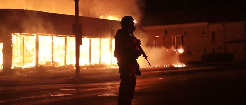 KENOSHA, WISCONSIN - AUGUST 24: A police officer stands guard in front of a burning business during a second night of rioting on August 24, 2020 in Kenosha, Wisconsin. Rioting as well as clashes between police and protesters began Sunday night after a police officer shot Jacob Blake 7 times in the back in front of his three children. (Scott Olson/Getty Images)