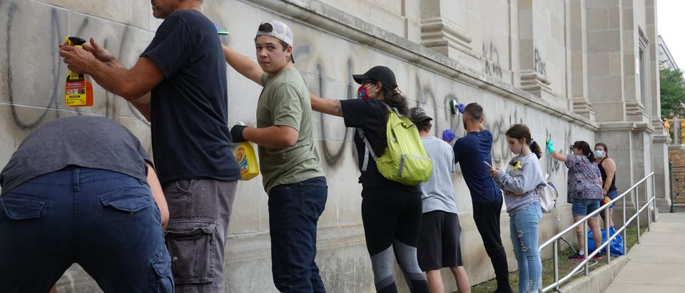 KENOSHA, WISCONSIN - AUGUST 25: Volunteers clean graffiti from a high school near the Kenosha County Courthouse following another night of unrest on August 25, 2020 in Kenosha, Wisconsin. Rioting as well as clashes between police and protesters began Sunday night after a police officer shot Jacob Blake, an unarmed Black man, seven times in the back in front of his three children. (Scott Olson/Getty Images)