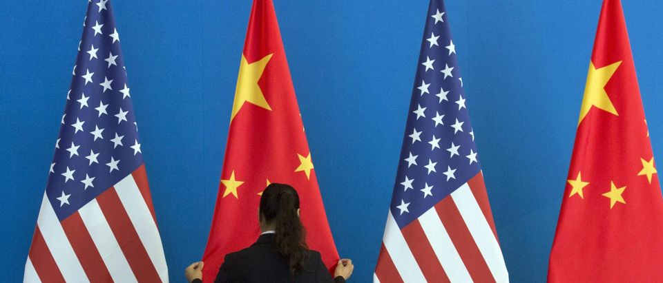 A Chinese woman adjusts a Chinese flag near US flags before the start of a Strategic Dialogue expanded meeting between China and the US during the US-China Strategic and Economic Dialogue held at the Diaoyutai State Guesthouse in Beijing on July 10, 2014. (NG HAN GUAN/AFP via Getty Images)