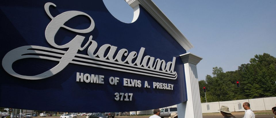 Fans walk by the entrance to Graceland,