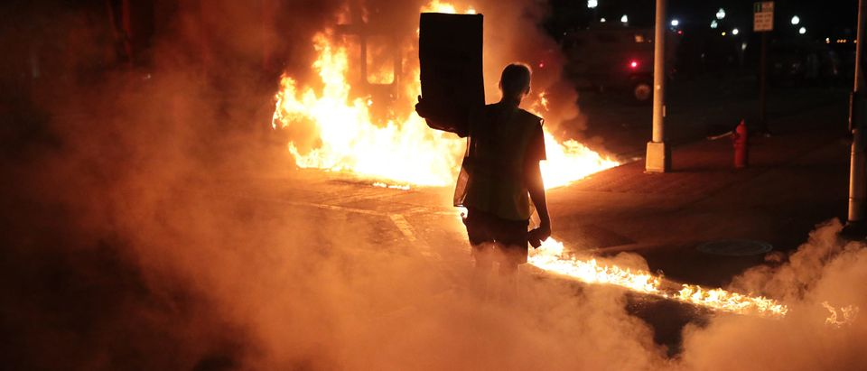 KENOSHA, WISCONSIN - AUGUST 24: Leaking diesel fuel from a burning garbage truck leaves a trail of fire in front of a protester during a second night of rioting on August 24, 2020 in Kenosha, Wisconsin. Rioting as well as clashes between police and protesters began Sunday night after a police officer shot Jacob Blake 7 times in the back in front of his three children. (Photo by Scott Olson/Getty Images)