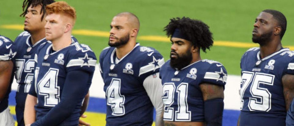 "INGLEWOOD, CALIFORNIA - SEPTEMBER 13: Dak Prescott #4 and Ezekiel Elliott #21 of the Dallas Cowboys stand with teammates and coaches on the field as Alicia Keys performs ""Lift Every Voice and Sing"" by video stream before the game between the Dallas Cowboys and the Los Angeles Rams at SoFi Stadium on September 13, 2020 in Inglewood, California. (Photo by Harry How/Getty Images)"