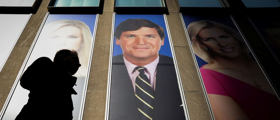 People pass by a promo of Fox News host Tucker Carlson on the News Corporation building in New York