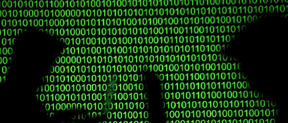 Silhouettes of laptop users are seen next to a screen projection of binary code are seen in this picture illustration