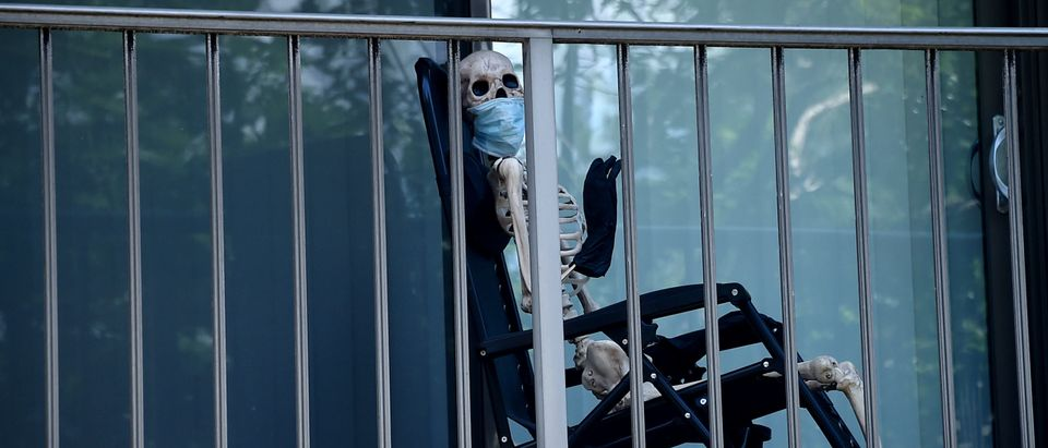 A Halloween skeleton wearing a face mask is on display on a balcony of an apartment in Washington, DC. (Photo by OLIVIER DOULIERY/AFP/Getty Images)