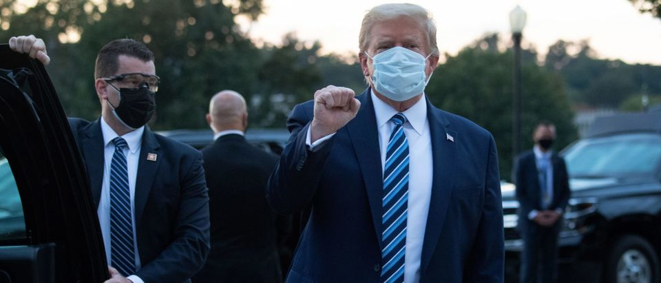 "US President Donald Trump pumps his fist as he leaves Walter Reed Medical Center in Bethesda, Maryland heading towards Marine One on October 5, 2020, to return to the White House after being discharged. - Trump announced Monday he would be ""back on the campaign trail soon"", just before returning to the White House from a hospital where he was being treated for Covid-19. (Photo by SAUL LOEB/AFP via Getty Images)"