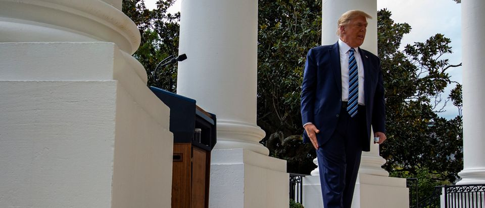 WASHINGTON, DC - OCTOBER 10: U.S. President Donald Trump walks back into the White House after addressing a rally in support of law and order on the South Lawn on October 10, 2020 in Washington, DC. The President is making his first in-person appearance after being cleared by his doctors following his diagnosis and treatment of the coronavirus approximately 10 days ago. (Photo by Samuel Corum/Getty Images)