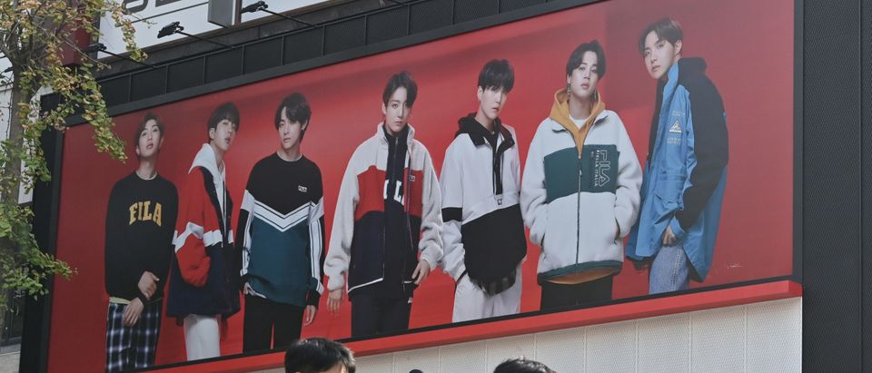 People walk past a commercial poster showing K-pop group BTS members at a shopping district in Seoul on October 12, 2020. (Photo by Jung Yeon-je / AFP via Getty Images)