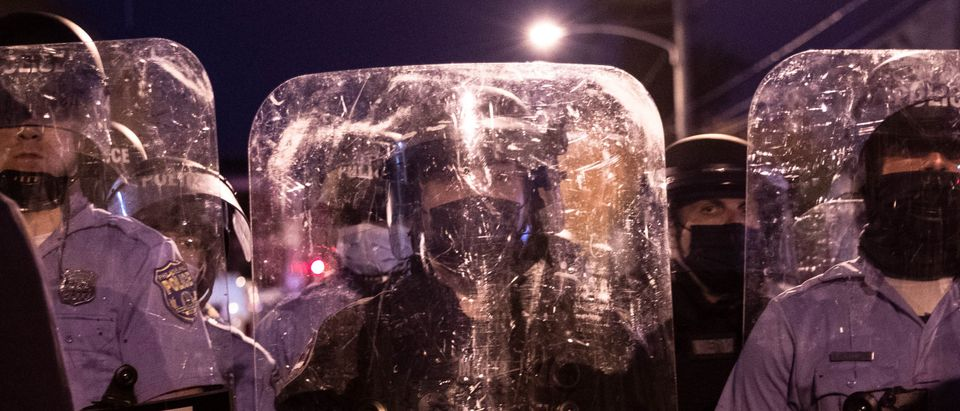 Police in riot gear face protesters marching through West Philadelphia on October 27, 2020, during a demonstration against the fatal shooting of 27-year-old Walter Wallace, a Black man, by police. (GABRIELLA AUDI/AFP via Getty Images)