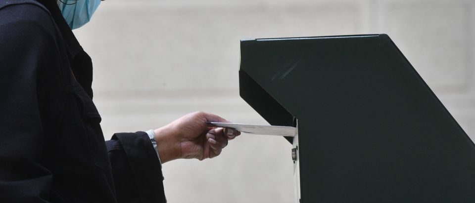 PHILADELPHIA, PA - OCTOBER 27: A woman deposits her ballot in an official ballot drop box at the satellite polling station outside Philadelphia City Hall on October 27, 2020 in Philadelphia, Pennsylvania. With the election only a week away, this new form of in-person voting by using mail ballots, has enabled tens of millions of voters to cast their ballots before the general election. President Donald Trump held three rallies throughout Pennsylvania yesterday to bolster his reelection prospects. (Mark Makela/Getty Images)