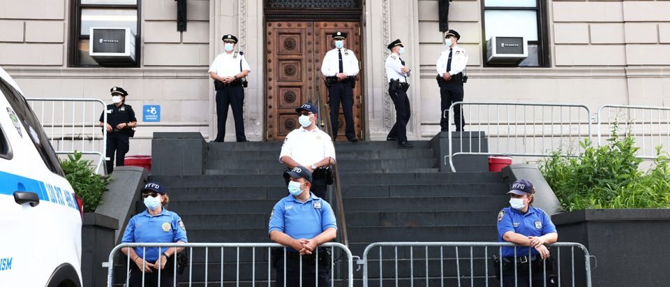 NEW YORK, NEW YORK - JULY 17: Police officers stand guard as protesters gather in front of the 120th NYPD precinct on the sixth anniversary of Eric Garner's death in Tompkinsville, Staten Island on July 17, 2020 in New York City. Garner was killed after being placed in a chokehold by former New York City Police officer Daniel Pantaleo during an arrest in 2014. (Michael M. Santiago/Getty Images)