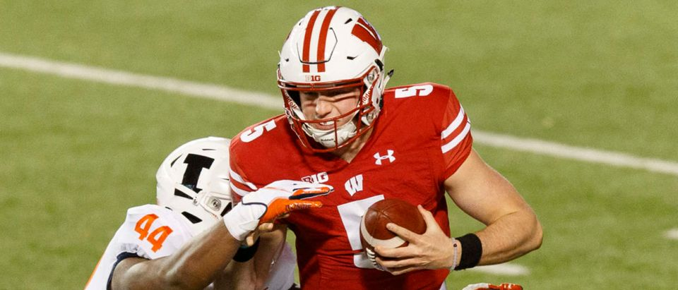 Oct 23, 2020; Madison, Wisconsin, USA; Wisconsin Badgers quarterback Graham Mertz (5) is tackled by Illinois Fighting Illini linebacker Tarique Barnes (44) during the second quarter at Camp Randall Stadium. Mandatory Credit: Jeff Hanisch-USA TODAY Sports via Reuters