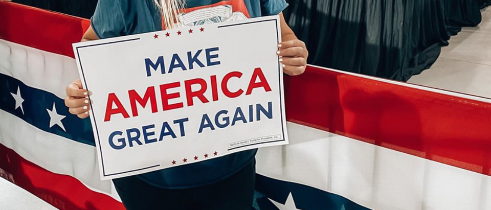Danielle Reiss attended a Sept. 13 rally for President Donald Trump. She is holding a 'Make America Great Again' poster while wearing a red 'Make America Great Again' hat. Reiss was allegedly fired for the post. (Screenshot/Instagram)