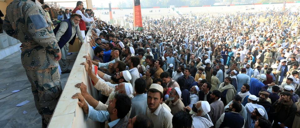 Afghan men wait to receive tokens needed to apply for the Pakistan visa, after people were killed in a stampede in Jalalabad