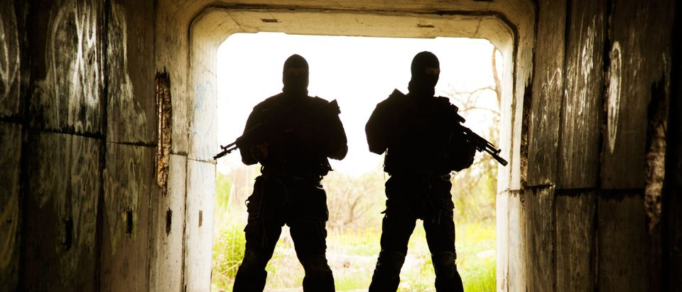 Silhouette of special forces operators with weapons in the tunnel (shutterstock)