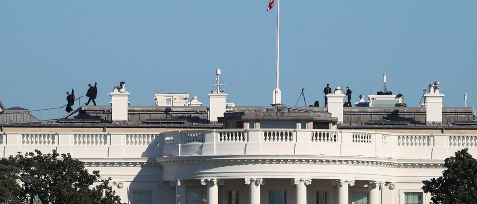 U.S. Secret Service counter snipers walk off of the rooftop during a shift change at the White House in Washington