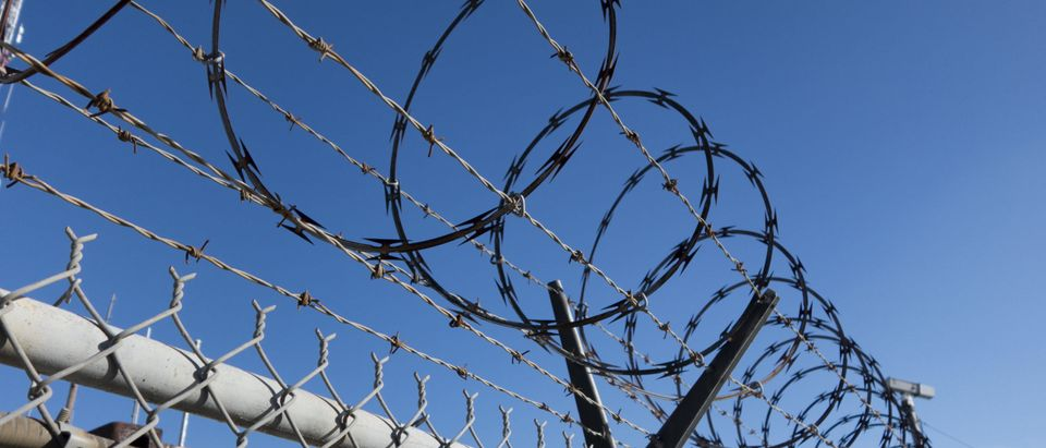 Barbed and razor wire on a fence with a security camera in the background by J Stephen Lee at Shutterstock