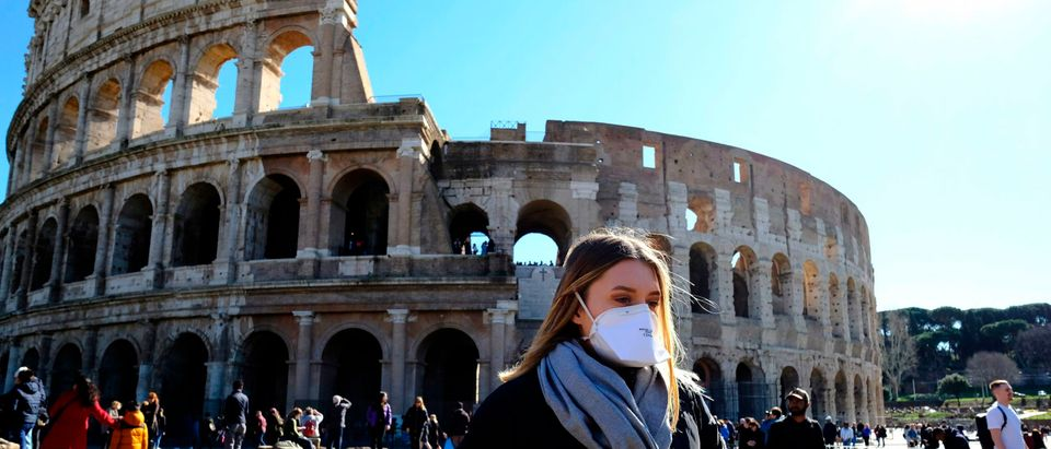Tourist wearing a protective respiratory mask tours outside the Colosseo monument (Colisee, Coliseum) in downtown Rome on February 28, 2020 amid fear of Covid-19 epidemic. - Since February 23, more than 50,000 people have been confined to 10 towns in Lombardy and one in Veneto -- a drastic measure taken to halt the spread of the new coronavirus, which has infected some 400 people in Italy, mostly in the north. (Photo by Andreas Solaro/AFP via Getty Images)