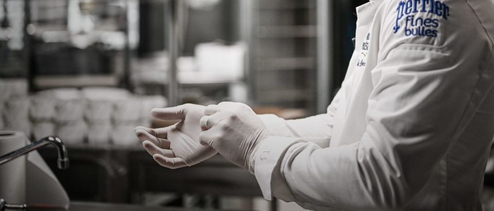 """French chef Eric Duquenne, former team leader in the kitchens of the Elysee Palace, adjusts latex gloves before packing dishes he cooked in his closed restaurant """"Les 3 Presidents"""" in Paris on March 25, 2020 before a delivery to an hospital for the medical personnel on the ninth day of a lockdown aimed at curbing the spread of the COVID-19 (novel coronavirus) in France. (Photo by Philippe Lopez/AFP via Getty Images)"""