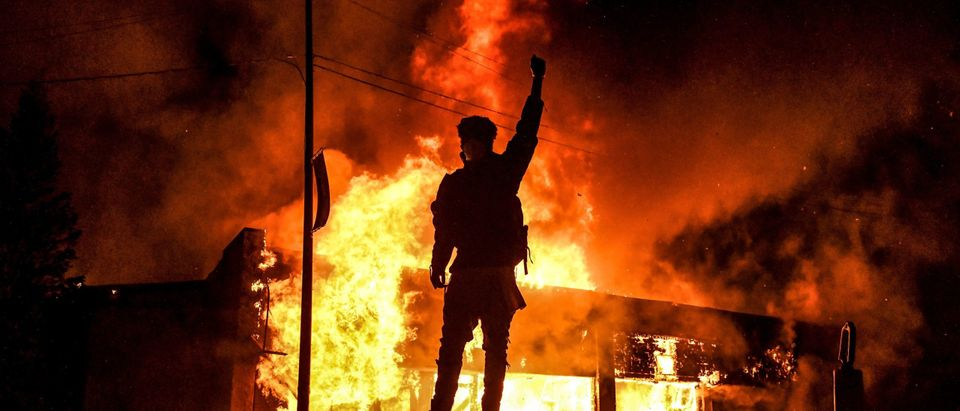 TOPSHOT - A protester reacts standing in front of a burning building set on fire during a demonstration in Minneapolis, Minnesota, on May 29, 2020, over the death of George Floyd, a black man who died after a white policeman kneeled on his neck for several minutes. - Violent protests erupted across the United States late on May 29 over the death of a handcuffed black man in police custody, with murder charges laid against the arresting Minneapolis officer failing to quell seething anger. (CHANDAN KHANNA/AFP via Getty Images)
