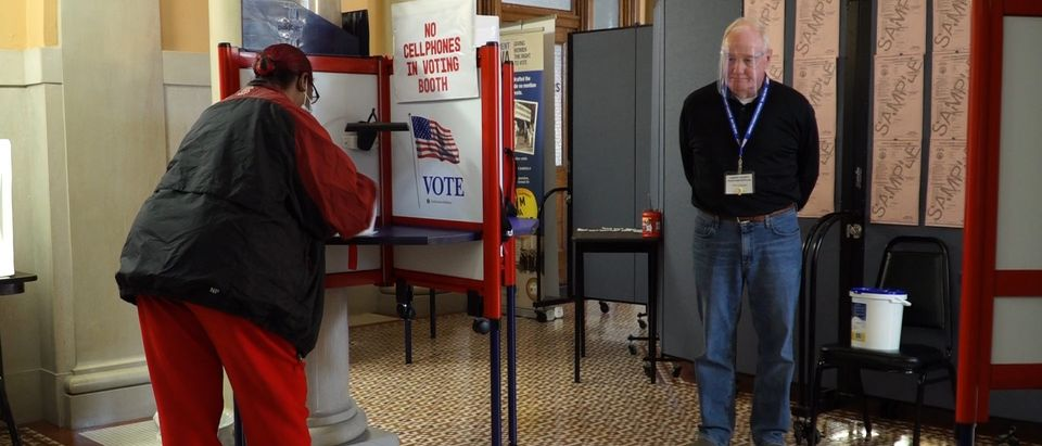 """A woman fills out her ballot at the early voting station in the courthouse of Jasper County in Newton, Iowa on October 15, 2020. - Though she's a Democrat, Michelle Smith understood Donald Trump's popularity in 2016 in her home state of Iowa. She lost her job along with 2,000 others when a factory for appliance manufacturer Maytag closed in 2007 in the city of Newton.""""I think people saw, 'Oh, he's not a politician. He's somebody new. He's a businessman. Let's give him a chance for economic development',"""" said Smith. She says her situation has, however, not improved since the New York real estate mogul's victory four years ago -- and in fact may have worsened. (ELEONORE SENS/AFP via Getty Images)"""