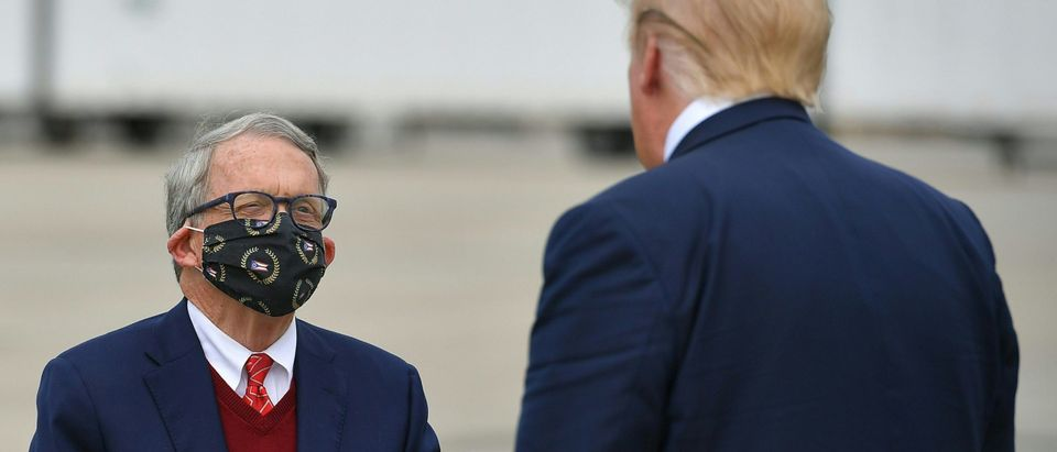 US President Donald Trump speaks with Ohio Governor Mike DeWine upon arrival at Rickenbacker International Airport in Columbus, Ohio on October 24, 2020. (Photo by Mandel Ngan/AFP via Getty Images)