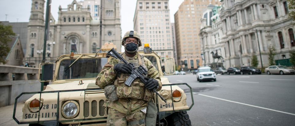 PHILADELPHIA, PA - OCTOBER 30: National Guard member Private First Class Clemens monitors activity surrounding Philadelphia City Hall on October 30, 2020 in Philadelphia, Pennsylvania. In response to widespread unrest in the aftermath of Walter Wallace Jr.'s death, the National Guard arrived this afternoon to various locations throughout the city. The 27-year-old Walter Wallace Jr, a father of nine children, who Philadelphia police officers claimed was armed with a knife, was fatally shot by at least 14 total rounds. (Mark Makela/Getty Images)