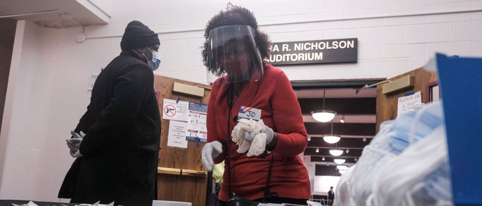 A poll worker wearing a mask and a face shield grabs a handful of latex gloves to hand out to voters a polling station in the King Arts Complex on November 3, 2020 in Columbus, Ohio. (Matthew Hatcher/Getty Images)