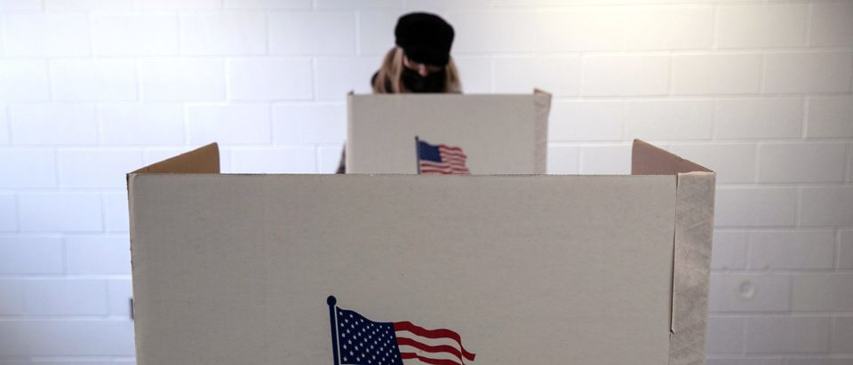 LANSING, MICHIGAN - NOVEMBER 02: A voter fills out her ballot on the last day of early voting at the Lansing City Clerk's office on November 02, 2020 in Lansing, Michigan. In 2016 U.S. President Donald Trump narrowly won Michigan, which is now a main battleground state. (John Moore/Getty Images)