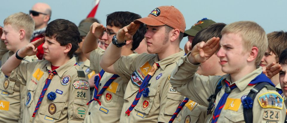 US boy scouts salute while listening to