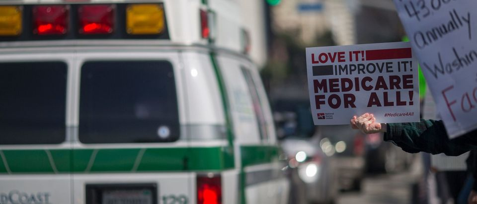 An ambulance passes people protesting Trump administration policies that threaten the Affordable Care Act, Medicare and Medicaid, near the Wilshire Federal Building on January 25, 2017 in Los Angeles (DAVID MCNEW/AFP via Getty Images)
