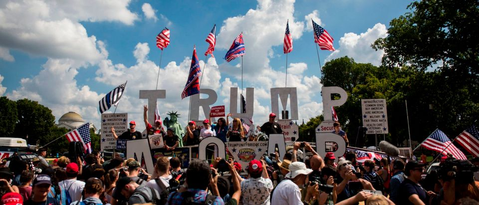"""Demonstrators wave national flags and placards during the pro-Trump 'Mother of All Rallies' on the National Mall in Washington, DC on September 16, 2017. - Supporters of President Donald Trump gathered in the US capital to show support of """"free-speech"""" dubbed the Mother of All Rallies. (Photo by Zach Gibson/AFP via Getty Images)"""